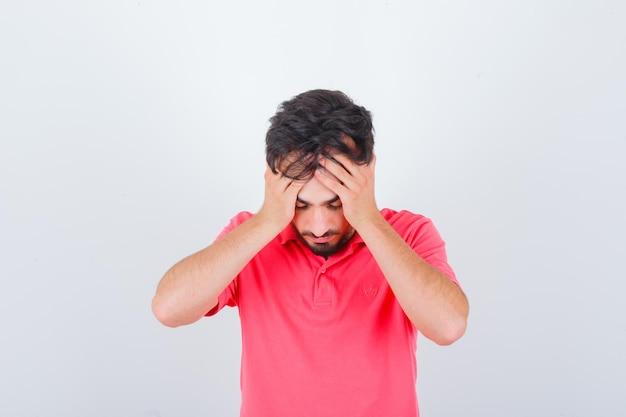 Giovane maschio che si tiene per mano sulla testa in maglietta rosa e sembra angosciato. vista frontale. Foto Gratuite
