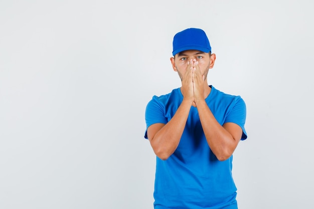 Молодой мужчина, взявшись за руки в молитвенном жесте в синей футболке
