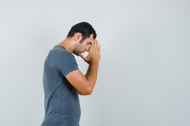 Молодой мужчина, взявшись за руки в молитвенном жесте в серой футболке и выглядя обнадеживающим