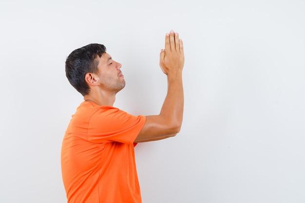 オレンジ色のtシャツで祈りのジェスチャーで手をつないで、希望に満ちた若い男性。 。