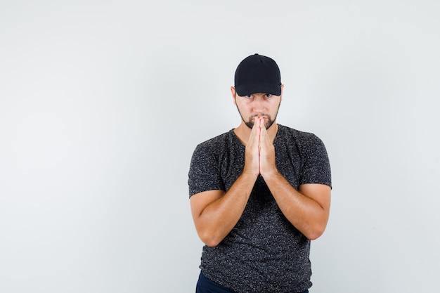Tシャツとキャップで祈りのジェスチャーで手をつないでいる若い男性