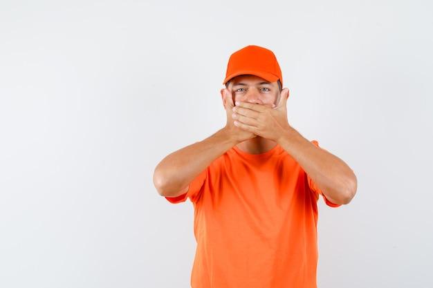 Giovane maschio che tiene le mani sulla bocca in maglietta arancione e cappuccio e che sembra spaventato