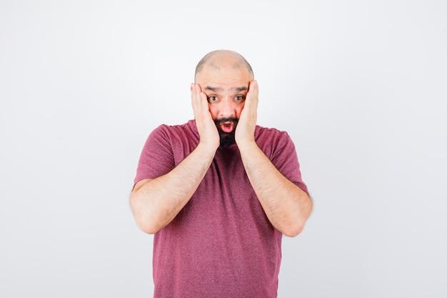 분홍색 티셔츠를 입은 뺨에 손을 대고 겁을 먹고 있는 젊은 남성.