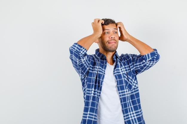 シャツを着て頭に手をつないで困惑している若い男性。正面図。