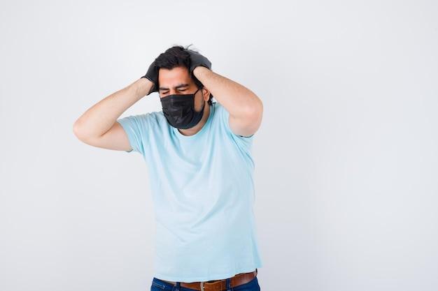Молодой мужчина держится за голову в футболке и выглядит раздраженным. передний план.