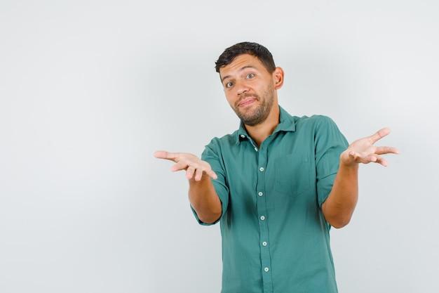Giovane maschio che tengono le mani nel gesto interrogativo in camicia