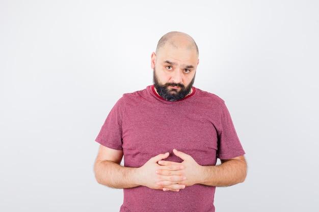 Молодой мужчина держится за руки вместе в розовой футболке и выглядит грустно, вид спереди.