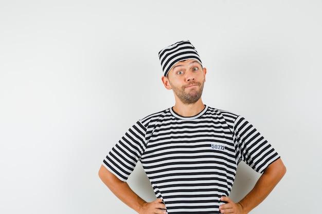 Giovane maschio che tiene le mani sulla vita in cappello della maglietta a strisce e che sembra carino