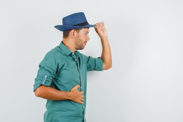 Giovane maschio che tiene cappello e sorridente in camicia