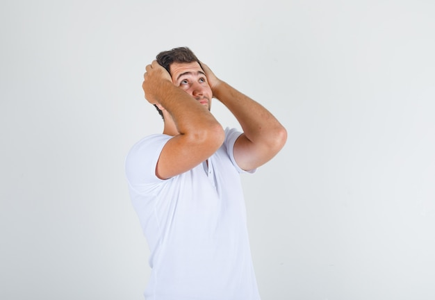 Young male holding head in hands and looking up in white t-shirt and looking worried
