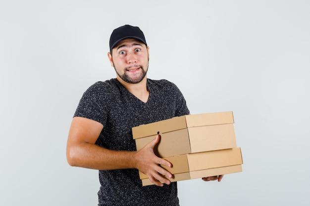 Tシャツとキャップの正面図で重い段ボール箱を保持している若い男性。