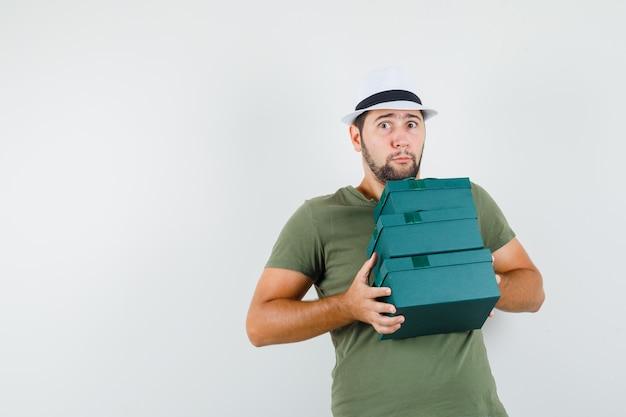 Giovane maschio che tiene le scatole presenti pesanti in maglietta e cappello verdi e che sembra perplesso