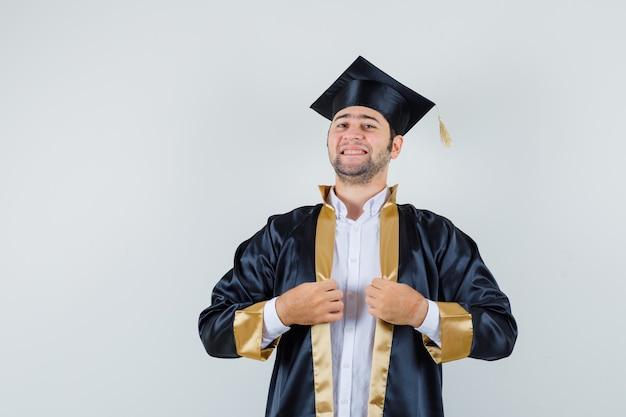 대학원 유니폼에 그의 가운을 들고 자랑스럽게, 전면보기를 찾고 젊은 남성.