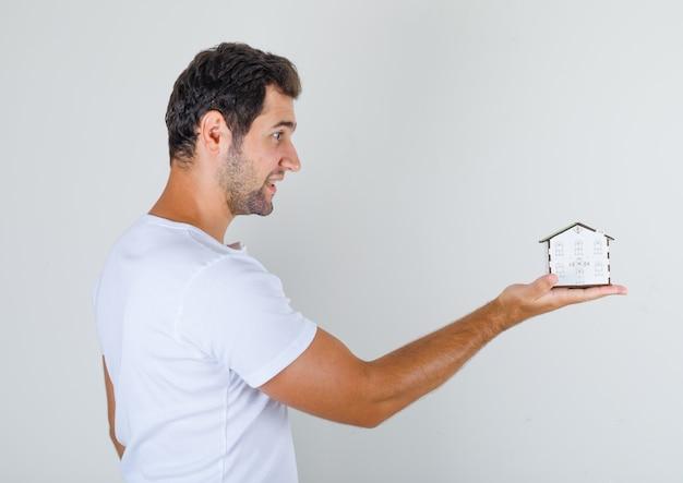 Молодой мужчина держит модель дома в белой футболке и выглядит обнадеживающим.