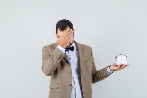 スーツの正面図で顔に手を持って家のモデルを保持している若い男性。