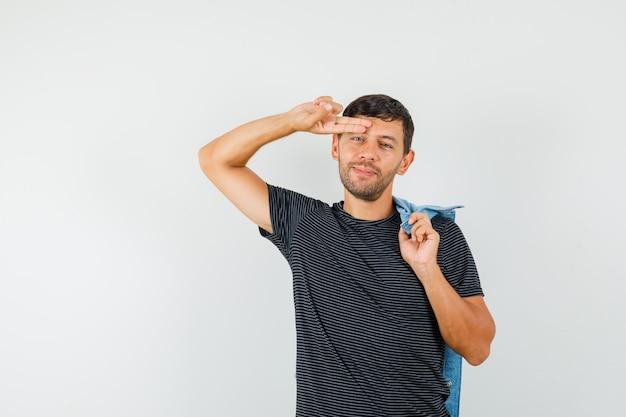 Молодой мужчина держит куртку на спине, держа пальцы на лбу в футболке и выглядит весело