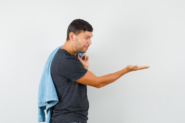 Молодой мужчина держит куртку на спине, глядя на пустую ладонь в футболке и выглядит подавленным