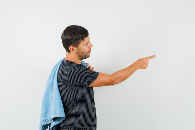 Молодой мужчина держит куртку на спине, указывая в сторону в футболке и выглядит позитивно