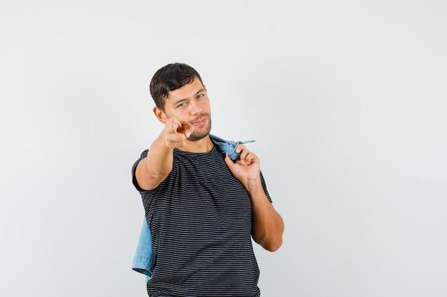 Молодой мужчина держит куртку на спине, указывая пальцами на камеру в футболке и выглядит весело