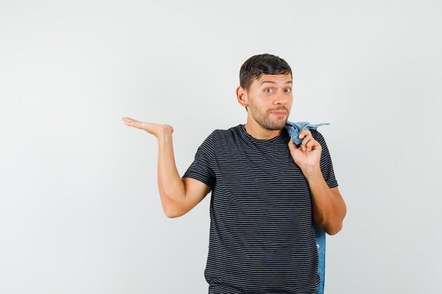 Молодой мужчина держит куртку на спине, разводя ладонь в футболке и выглядит весело