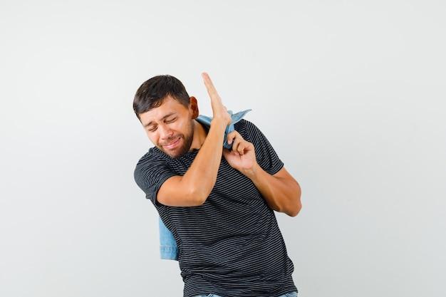 Молодой мужчина держит куртку, показывая жест остановки в футболке и выглядит грустно