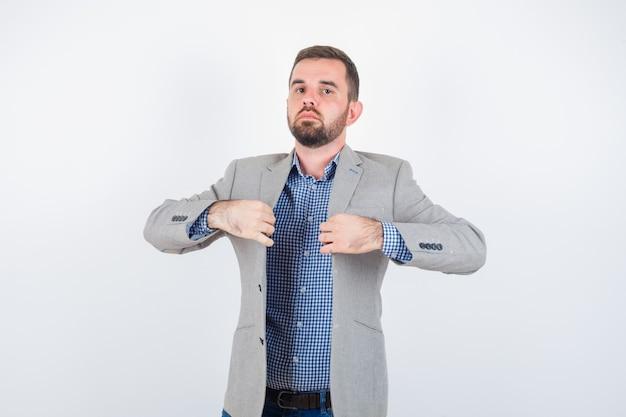 Giovane maschio che tiene i risvolti mentre posa in camicia, jeans, giacca e sembra serio, vista frontale.