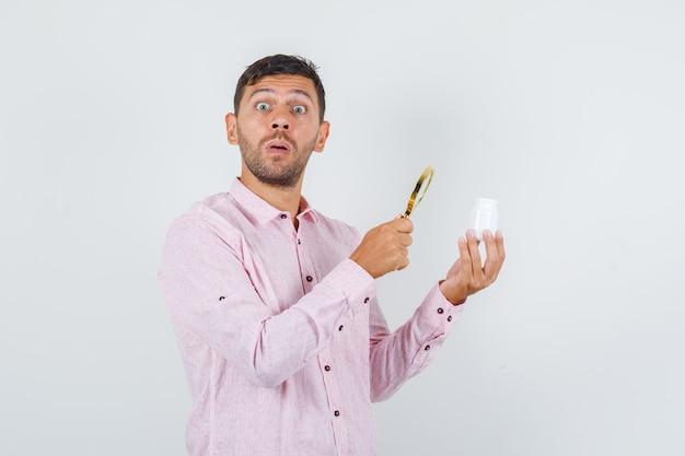 Молодой мужчина держит лупу над бутылкой таблетки в рубашке и выглядит удивленным, вид спереди.