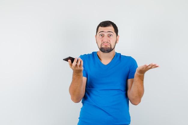 青いtシャツを着て携帯電話を持って混乱しているように見える若い男性