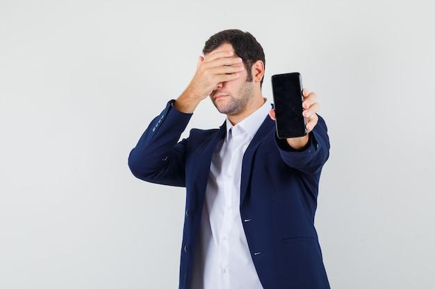 シャツに携帯電話を保持している若い男性
