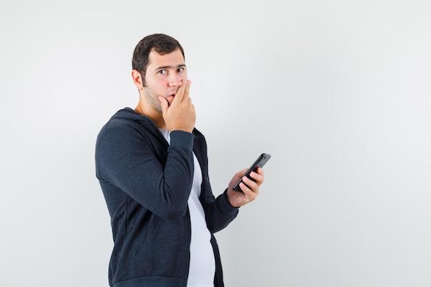 T- 셔츠, 재킷에 휴대 전화를 들고 놀 찾고 젊은 남성. 전면보기.