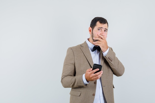 Young male holding mobile phone in suit and looking forgetful. front view.