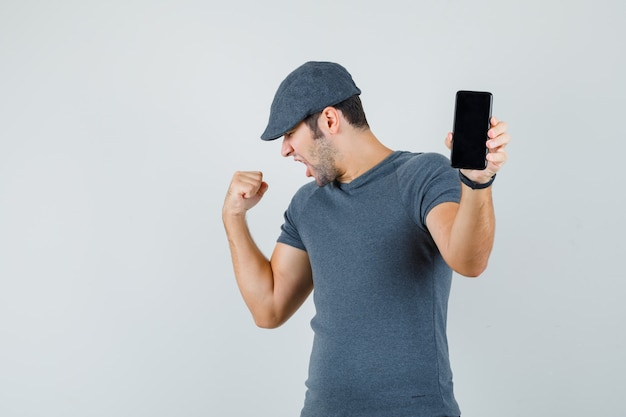 Young male holding mobile phone in t-shirt cap and looking lucky