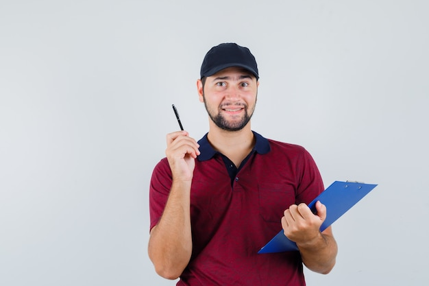 Young male holding notebook and pen in red t-shirt,black cap and looking smart , front view.