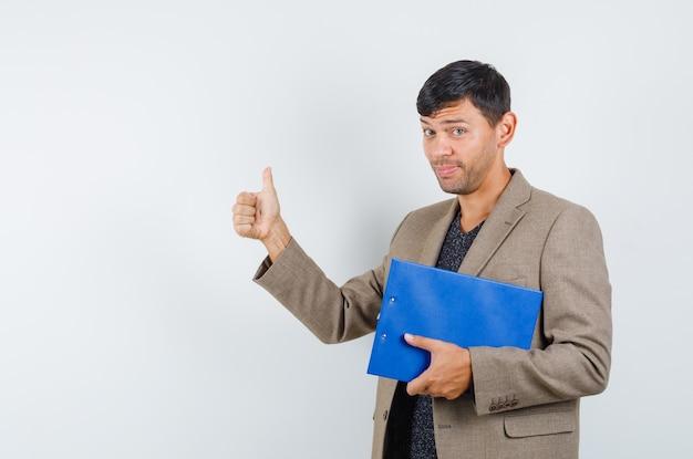 灰色がかった茶色のジャケット、黒のシャツで親指を表示し、感謝している、正面図を表示しながらノートを保持している若い男性。