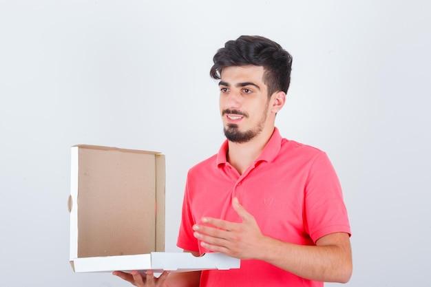젊은 남성 지주 t- 셔츠에 피자 상자를 열고 예쁜 찾고. 전면보기.