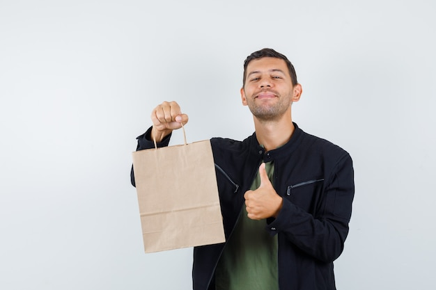 Young male holding paper bag with thumb up in t-shirt, jacket and looking cheerful. front view.