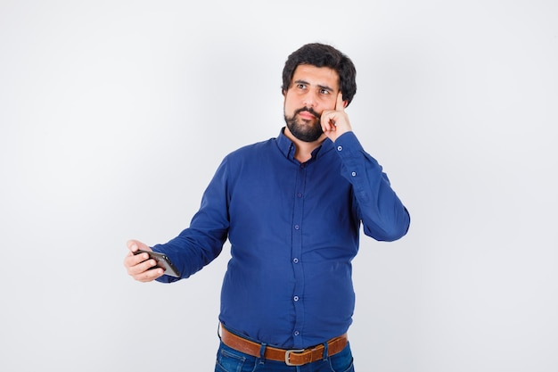 Young male holding phone while thinking in royal blue shirt , front view.