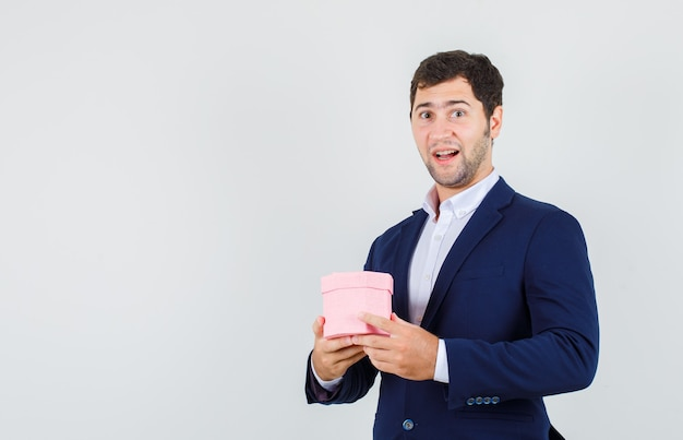 スーツにピンクのギフトボックスを保持し、陽気に見える若い男性、正面図。