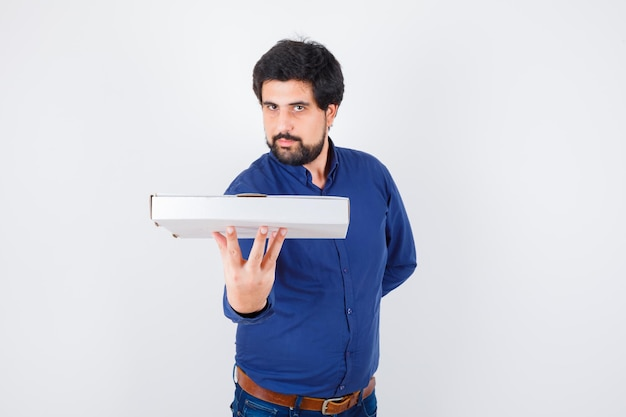 Young male holding pizza box in shirt, jeans and looking confident. front view.