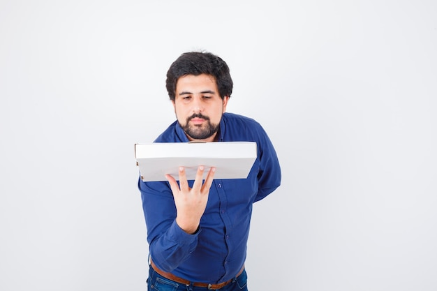Young male holding pizza box in shirt, jeans and looking confident , front view.