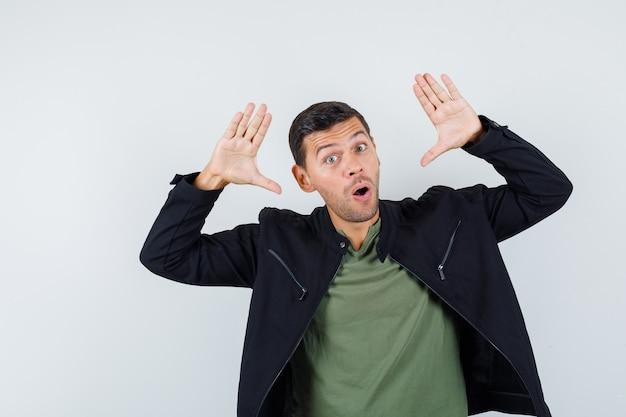 Giovane maschio che tiene le palme sollevate in aria in t-shirt, giacca e guardando divertito. vista frontale.