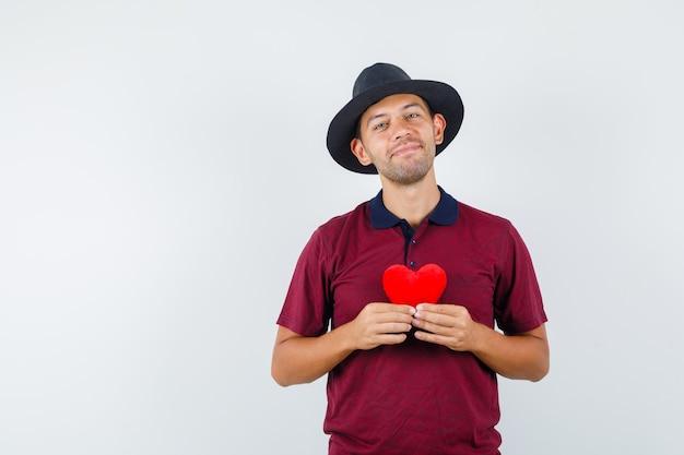 Giovane maschio che tiene cuore rosso in camicia rossa, cappello nero e che sembra romantico, vista frontale.
