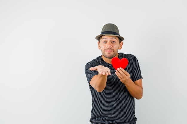 Young male holding red heart stretching hand in t-shirt hat and looking merry