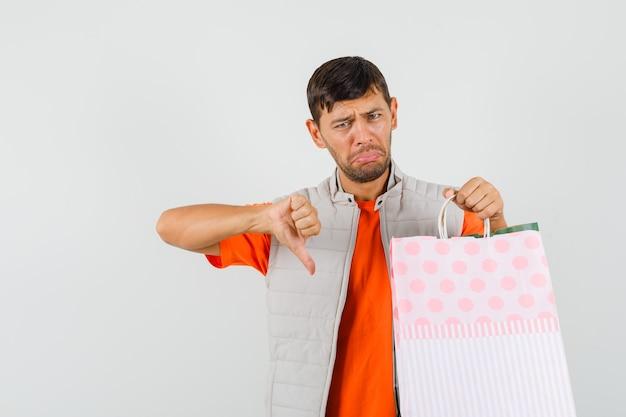 ショッピングバッグを持って、tシャツ、ジャケットで親指を下に見せて、悲しそうに見える若い男性、正面図。