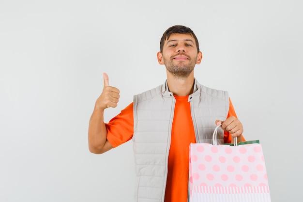 Giovane maschio che tiene i sacchetti della spesa, mostrando il pollice in su in maglietta, giacca e guardando gioviale, vista frontale.