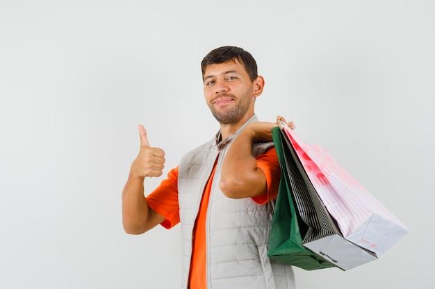 Giovane maschio che tiene i sacchetti della spesa, mostrando il pollice in su in maglietta, giacca e guardando allegro. vista frontale.