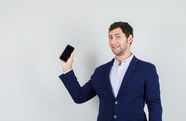 スーツにスマートフォンを持って、陽気に見える若い男性、正面図。