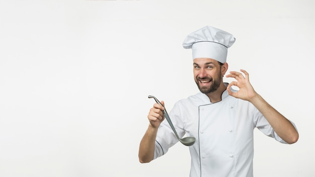 Young male holding soup from ladle making tasty sign isolated on white background