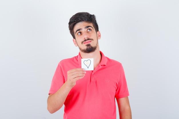 Giovane maschio che tiene una nota adesiva in maglietta e sembra fiducioso, vista frontale.