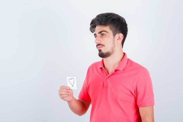 Tシャツで目をそらし、思慮深く、正面図を見ながら付箋を保持している若い男性。